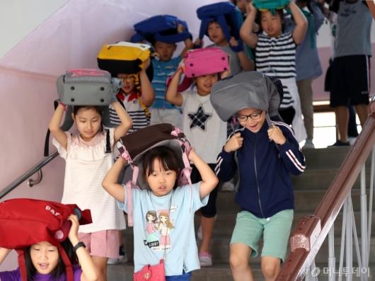 [사진]가방으로 머리 보호해요