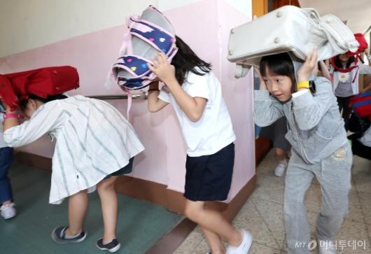 [사진]지진 대피 훈련하는 학생들
