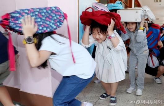 [사진]몸 낮추며 머리 보호하는 초등생들