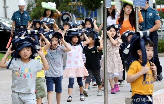 [사진]머리 보호하며 지진 대피