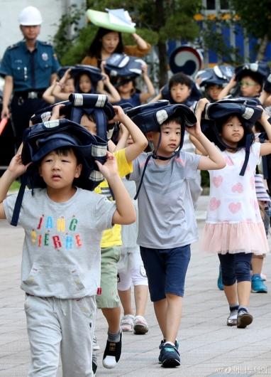 [사진]가방으로 머리 보호하는 어린이들