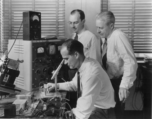 트랜지스터 개발자 3인. 쇼클리(앉은 사람), 바딘(왼쪽에 서 있는 사람), 브래튼이 최초의 트랜지스터를 들여다보고 있다. <br /> 자료제공: 알카텔-루슨트 벨랩