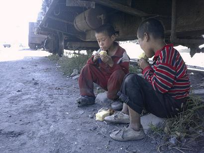 ↑2006년 함경북도의 한 도시에서 꽃제비 아이들이 구걸한 빵을 기차길 부근에서 먹고 있다. ⓒ좋은벗들