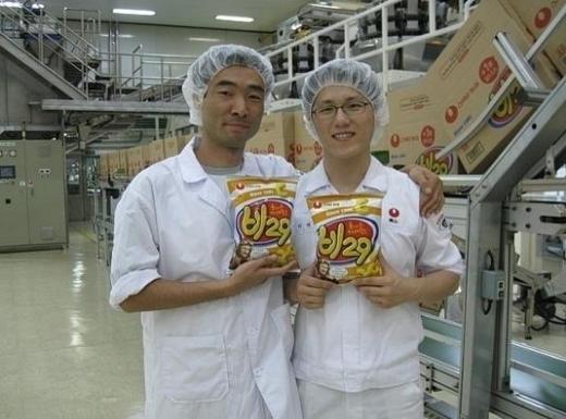 ▲'비29'의 연구·개발을 맡은 농심의 박준상 차장(왼쪽)이 공장에서 18년만에 다시 선보인 비29의 첫번째 생산품을 들고 웃고 있다. 박 차장은 이 사진을 '카레맛 과자 비29의 생산을 바라는 카페'에도 올렸다.
