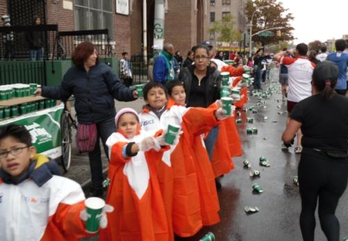 ↑ 뉴욕마라톤 주로에 나와 주자들에게 음료수를 건네며 응원하고 있는 아이들.