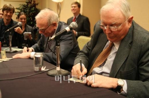 ↑ 2009년 미 네브래스카주 오마하에서 열린 주주총회 당시 기자간담회에서 지폐에 서명해주고 있는 워런 버핏 버크셔 해서웨이 회장(왼쪽)과 찰리 멍거 부회장.[사진=김준형 기자]