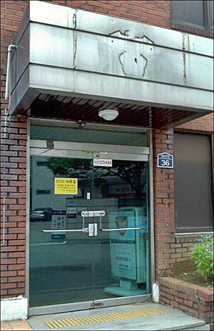 ↑ 용산구의 한 치안센터. 건물을 폐쇄하면서 경찰 현판을 떼내 흔적만 남아있다. 잠긴 문 뒤로는 민원안내 입간판이 놓여있다.(사진= 김상희 기자)