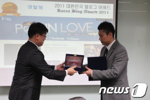 2011블로그어워드에서 특별상을 받고 있는 원인학 경위(오른쪽).  News1