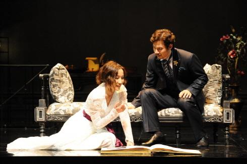↑연극 '헤다 가블러', 신혼여행 사진을 함께 보고 있는 헤다와 뢰브보르그 ⓒ명동예술극장