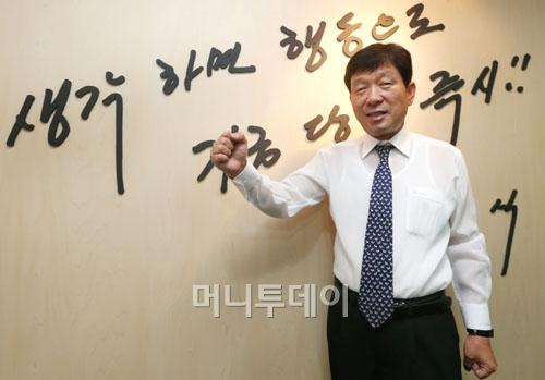 """↑""""생각하면 행동으로, 지금 당장 즉시!""""라고 쓰여진 벽 앞에 서 있는 김 회장. ⓒ홍봉진 기자"""