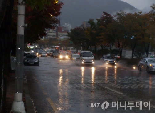 ↑27일 부산시내 모습. 폭우로 자동차들이 물길을 가르며 운행하고 있다.ⓒ송학주
