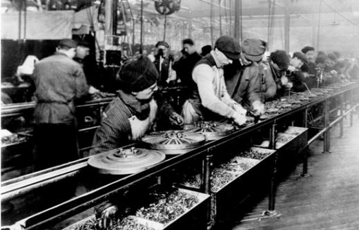 1913년 포드공장 컨베이어 벨트에서 '모델T'의 플라이 휠을 조립하는 노동자들 모습. 헨리 포드는 시카고의 한 도살장에서 궤도장치에 거꾸로 매달린 소의 몸통을 노동자들이 쭉 늘어서서 부위별로 고기를 발라내는 모습을 보고 컨베이어벨트에 대한 영감을 얻었다. /사진출처:AP