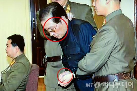 (서울=뉴스1)  북한 조선중앙통신은 최근 숙청이 결정된 장성택 전 북한 국방위원회 부위원장이 지난 12일 열린 특별군사재판 후 즉각 사형을 당했다고 13일 밝혔다.  사진은 포승줄에 양 손이 묶인 장성택이 국가안전보위부원들에게 붙들린 채 법정에 선 모습. 원내는 구타당한 흔적(YTN 화면캡쳐) 2013.12.13/뉴스1