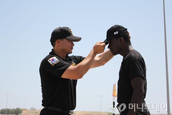 이춘성 교관이 해외 파견 훈련 당시 오만 현지 경찰에게 모자를 씌워주는 모습./사진 제공=이춘성 서울지방경찰청 기동본부 훈련교관