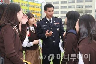 문승민 서울서부경찰서 학교폭력전담경찰관(경사)이 서울 충암중학교 운동장에서 학생들과 이야기를 나누고 있다./사진=이동훈 기자