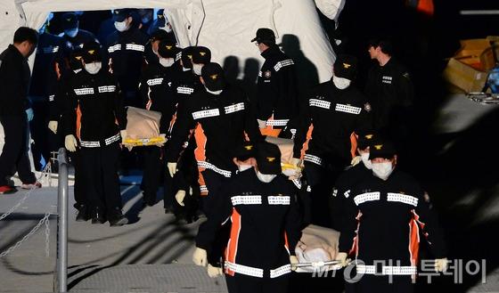 (진도=뉴스1) 양동욱 기자 세월호 여객선 침몰 사고 발생 엿새째인 21일 오후 전남 진도 팽목항 선착장에서 고인들의 시신이 운구되고 있다.<br><br>이날 상당수 실종자들이 갇혀 있을 것으로 추정된 세월호 3~4층에서 시신이 다수 발견됐다. 2014.4.21/뉴스1