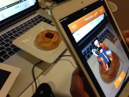 더블미의 '3차원 재구성' 애플리케이션 '4CAST' 시연 모습. 앱을 실행한뒤 스마트폰으로 촬영하자 화면상에서 빵 위로 3D 캐릭터 영상이 튀어올라 재생된다./사진=이해진 기자