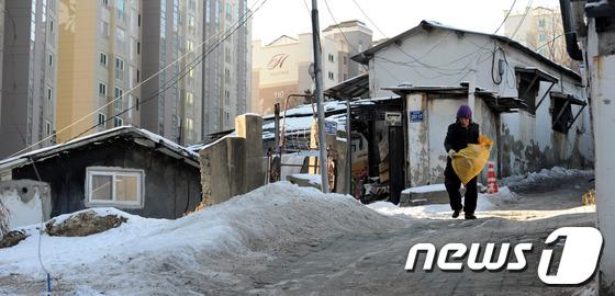 서울 동작구에서 한 남성이 쓰레기 봉투를 들고 눈 내린 길을 걷고 있다./ 사진=뉴스1