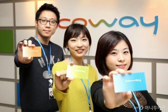 코웨이 직원들이 지난 2013년 그룹에서 분리하며 바뀐 CI와 함께 사진촬영을 하고 있다./사진제공=코웨이