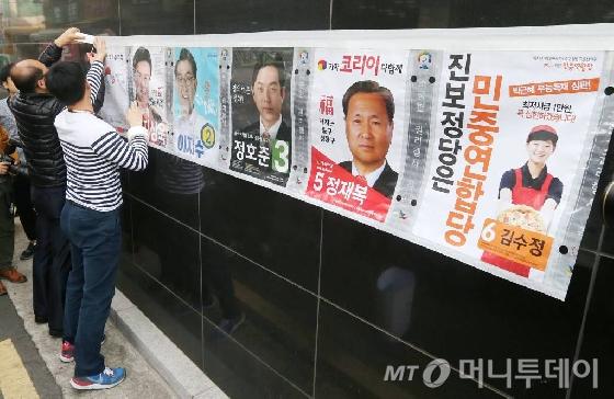 4.13 총선 공식 선거운동이 시작된 31일 오전 서울 을지로4가에서 중구청 직원들이 한 건물 외벽에 선거벽보를 붙이고 있다.