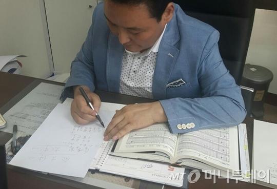 사단법인 한국작명가협회 김기승 이사장이 기자의 사주를 바탕으로 새 이름을 짓고 있다./사진=백승관 기자