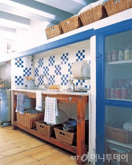 파란색 페인트칠을 통해 포인트를 준 싱크대와 라탄 바구니를 매치해 여름철 인테리어를 한 부엌 예시