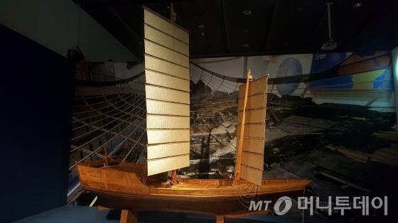'신안해저선에서 찾아낸 것들' 전시실 맨 앞에 서 있는 배 조형물. 원래 크기의 10분의 1로 축소된 모형이다. 실제 배는 길이 34미터, 폭 11미터, 중량 200톤급 이상으로 중국 푸젠 성에서 제작된 것으로 추정한다. 해저선은 1323년 중국 경원항을 출발해 하카타 항으로 가던 중 제주 해역에서 표류하다 신안 앞바다에서 침몰했을 가능성이 높다./사진제공=갤럭시6, 신혜선