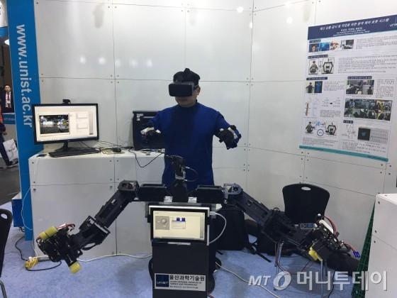 본지 정보미디어과학부 류준영 기자가 센서가 부착된 수트와 손가락의 움직임을 측정하는 특수 장갑 등을 착용하고 '원격 조종 재난현장 대응 로봇'을 시연하고 있다. 이 로봇은 배준범 울산과학기술원(UNIST) 기계 및 원자력공학부 교수 연구팀이 개발했다/사진=UNIST <br>
