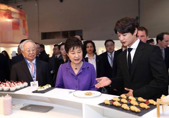 프랑스를 국빈 방문 중이던 박근혜 대통령이 6월 2일 오후(현지시간) 파리 아르코 호텔 아레나에서 CJ가 개최하는' KCON 2016 프랑스'에 참석해 한식 홍보부스에서 샤이니 멤버 민호와 붕어빵을 살펴보고 있다. /사진=뉴스1