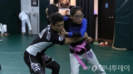 선생님들이 괴한이 허리를 끌어안을 경우 벗어나는 방법을 가르쳐주고 있다./사진=박지윤 기자