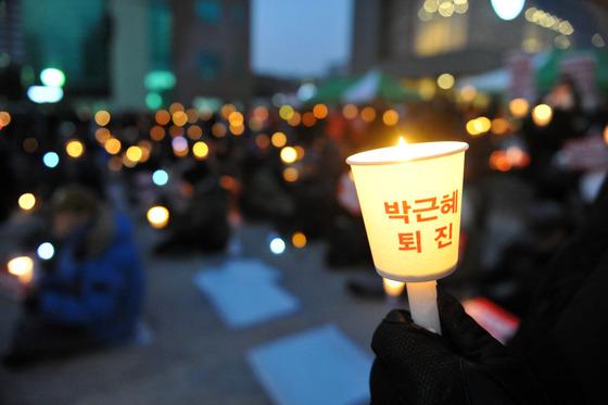 31일 강원 춘천시 김진태 의원 사무실 인근에서 열린 '박근혜 즉각 퇴진 촛불집회'에서 시민들이 촛불을 들고 구호를 외치고 있다./ 사진제공=뉴스1