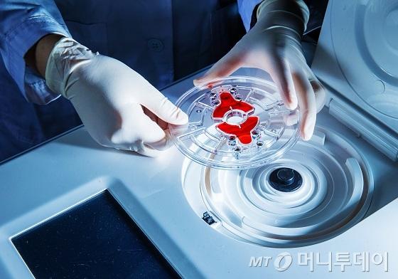 혈액을 넣은 FAST 랩온어디스크와 이를 회전시킬 장비/사진=UNIST