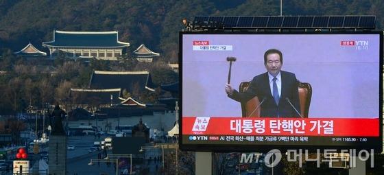 박근혜 대통령에 대한 탄핵소추안이 가결된 지난해 12월 9일 청와대가 보이는 서울 중구 태평로 프레스센터 앞 대형 전광판에 국회 표결 결과가 생중계 되고 있다. /사진=뉴스1