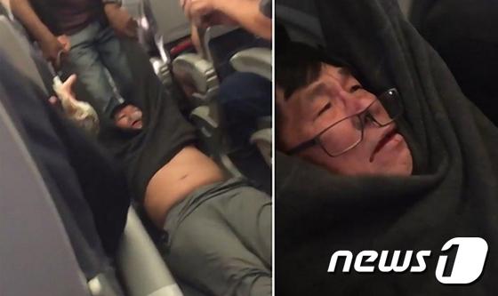 유나이티드항공이 탑승객을 무력으로 끌어내리고 있다. 승객은 버티는 과정에서 팔걸이에 부딪혀 입에 피를 흘렸다./사진=뉴스1