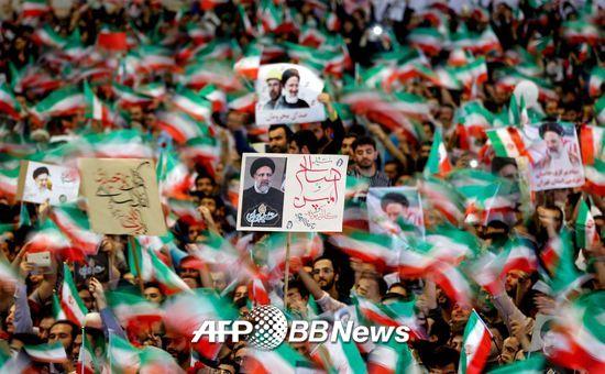 16일(현지시간) 이란 수도 테헤란의 이맘 호메이니 모스크에서 열린 보수파 대선후보 에브라힘 라이시 지지 집회에서 지지자들이 이란 국기와 라이시 후보의 사진을 흔들고 있다./AFPBBNews=뉴스1