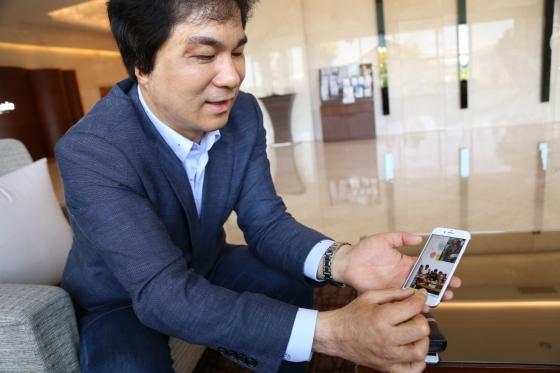 유웅환 전 민주당 4차산업혁명 공동위원장이 전날 동료들과 생일파티한 사진을 보여주며 환하게 웃고 있다./사진= 김민우 기자