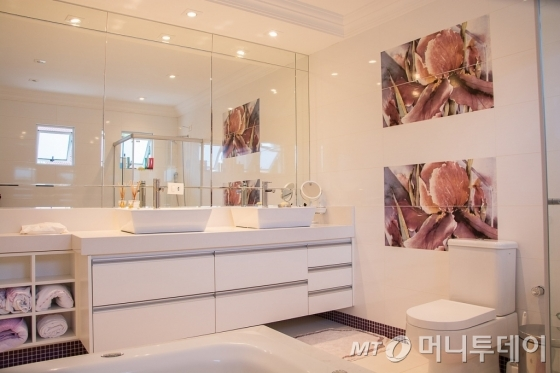 한쪽 벽에 면적이 큰 거울을 붙이고 전반적으로 흰색계열의 밝은색상을 활용해 공간을 더욱 넓어보이게 연출한 욕실 인테리어의 예