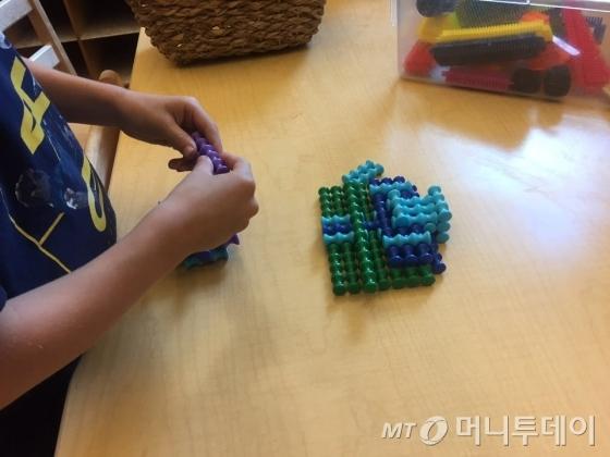 13일(현지시간) 오전 미국 아이오와주 디모인 사이언스 센터(science center) 유치원에서 어린이가 블록을 쌓고 있다. 굉장히 작은 이 블록을 쌓으려면 아이가 굉장히 집중해야 한다. 집중력과 함께 기본 엔지니어링 기술을 익힐 수 있도록 마련된 놀이다./사진=아이오와(미국) 방윤영 기자