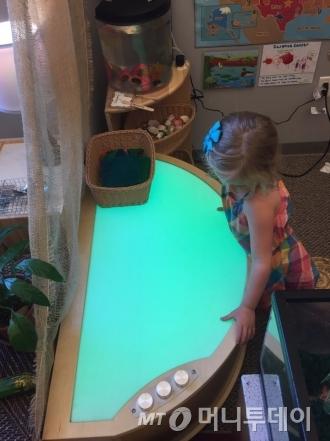 13일(현지시간)  미국 아이오와주 사이언스 센터(science center) 유치원에서 어린이가 라이트 테이블(빛이 나오는 테이블)을 조작하며 놀고 있다. 버튼을 조절해서 빛 색깔을 바꿔보는 놀이다. 아이는 이 놀이를 통해 빛의 변화를 배울 수 있다./사진=아이오와(미국)=방윤영 기자