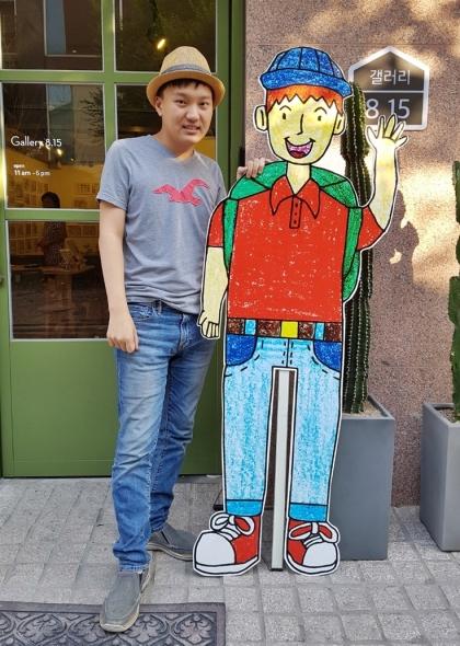 자폐증의 일종인 '서번트 증후군'을 진단 받은 화가 캘빈 신이 그림으로 그린 자신의 모습 옆에 섰다. 오는 27일까지 서울 서교동 '갤러리815'에서 열리는 전시를 통해 그의 그림을 만날 수 있다. /사진=박다해 기자
