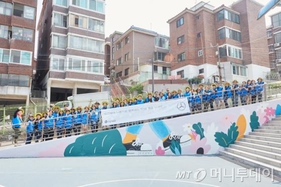 메르세데스-벤츠 사회공헌위원회가 지난 17일 서울 은평구 상신초등학교에서 '안심 학교 담벼락 그리기' 봉사활동을 진행했다. 참여한 임직원들이 사진을 찍고 있다./사진=메르세데스-벤츠 코리아