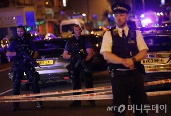 19일(현지시간)  영국 런던 북부 핀즈버리 파크 인근 인도에서 테러로 의심되는 차량 1대가 돌진해 수명이 다친 현장에 경찰이 경비를 하고 있다./AFP=뉴스1