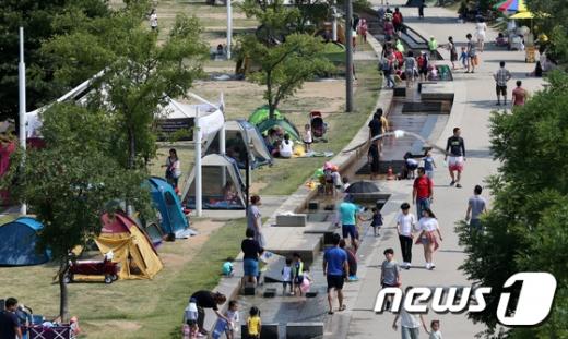 폭염특보가 지속되며 무더운 날씨가 이어지는 가운데 서울 여의도 한강공원에서 시민들이 텐트를 쳐놓고 물놀이를 하고 있다. 2017.6.18/뉴스1 © News1 안은나 기자