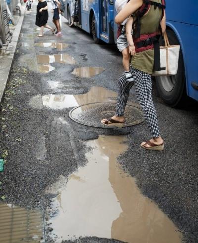 포트홀에 고인 물웅덩이는 운전자와 보행자의 안전을 위협한다. /사진=뉴스1