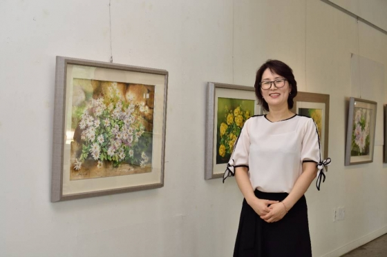 민은경 한국야쿠르트 충청 온양지점 아줌마가 지난 5월 미술 전시회에서 자신이 그린 꽃 그림 앞에서 기념촬영 하고 있다./사진제공=한국야쿠르트