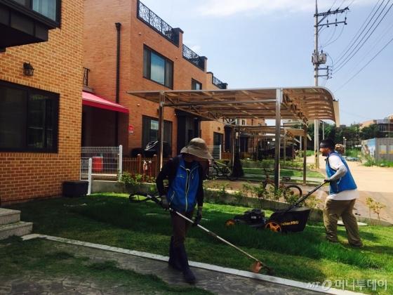 신축 임대주택 앞 잔디를 관리업체 직원들이 손질하고 있다. /사진=남궁민 기자