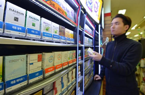 정부가 담뱃값 인상 효과를 발표한 7일 한 서울시내 편의점에서 고객이 담배를 고르고 있다.  기획재정부 발표에 따르면 지난해 담배 판매량은 직전년도 대비 23.7%(10억3000갑) 줄어든 33억3000갑, 담배 세수는 10조5000억원으로 직전년도 대비 3조6000억원 증가한 것으로 집계됐다. 이는 세수는 3조6000억 증가, 판매량은 24% 감소한 수치다. 2016.1.7/뉴스1  <저작권자 © 뉴스1코리아, 무단전재 및 재배포 금지>