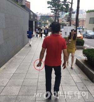 서울 중구 서울스퀘어 인근 도로에서 한 남성이 걸어가며 담배를 피우고 있다./사진=남형도 기자