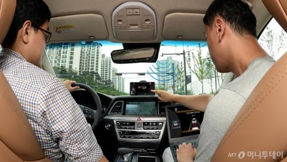 현대∙기아차 연구원들이 차량 내부에서 '교차로 교통신호 정보 서비스'를 테스트하고 있다./사진제공=현대·기아차