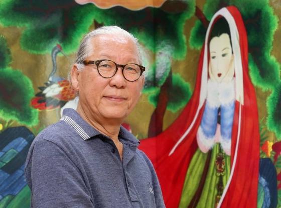 김동화 한국만화진흥원 이사장이 자신의 작품 '기생이야기'(1998)를 배경으로 사진 촬영을 하고 있다. /파주=홍봉진 기자<br />